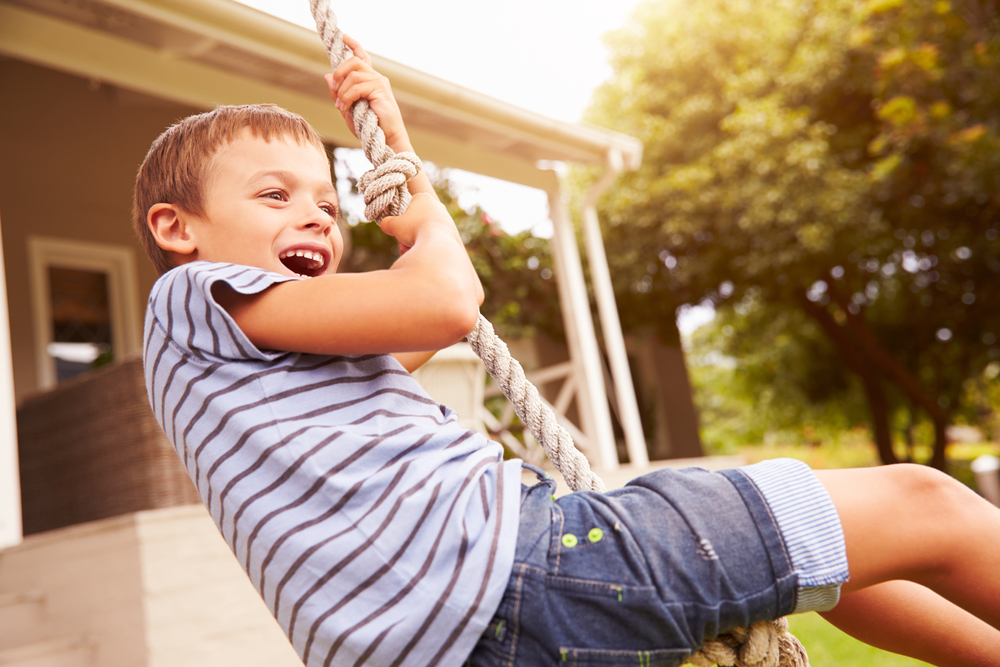 happy-young-boy-playing-on-swing
