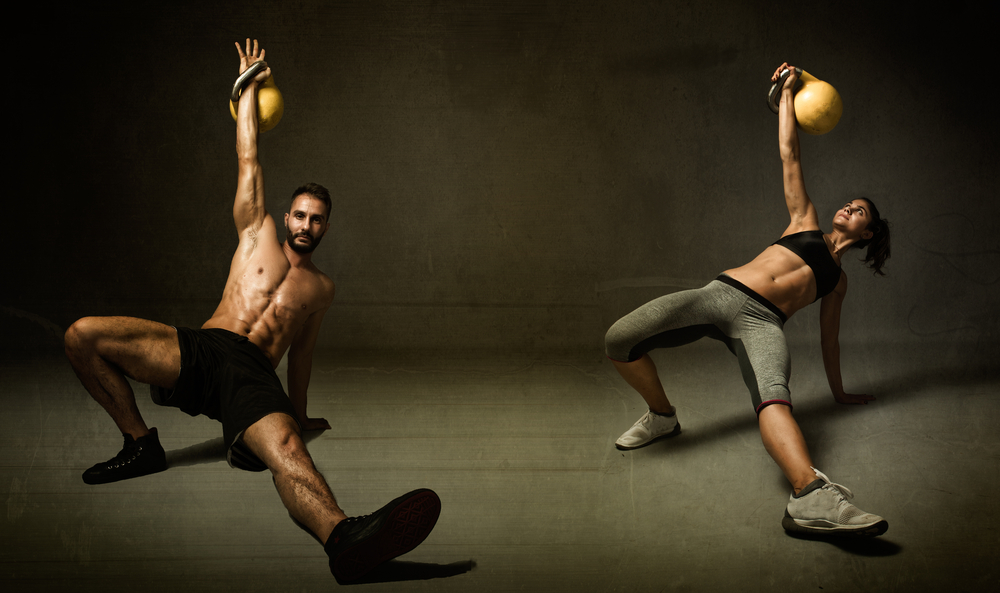 attractive-man-and-woman-doing-kettleball-exercise