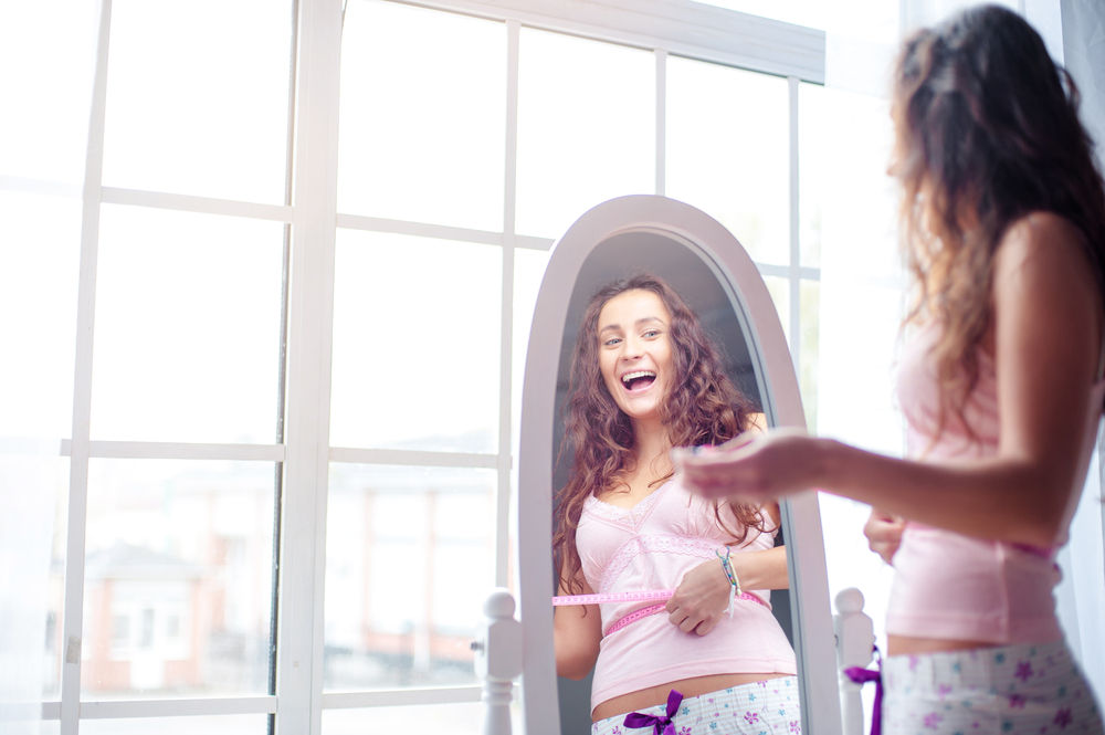 girl-happy-infront-of-mirror-after-losing-weight
