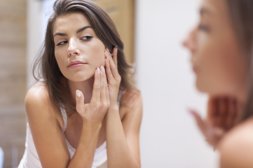 girl-looking-in-mirror-for-acne