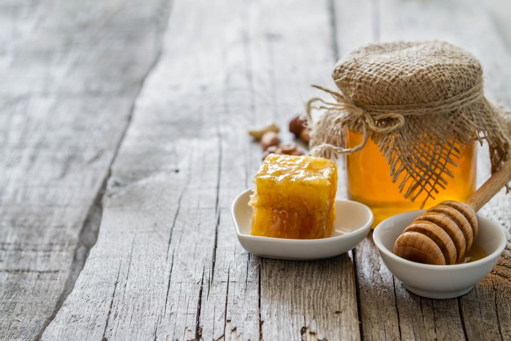 honey-and-honeycomb-on-wooden-floor