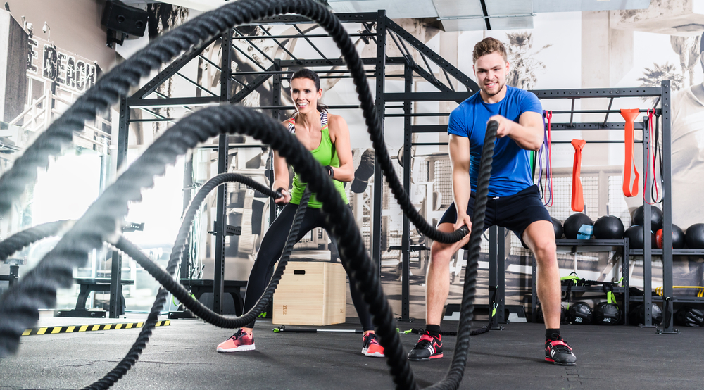 man-and-woman-doing-battling-rope-in-gym