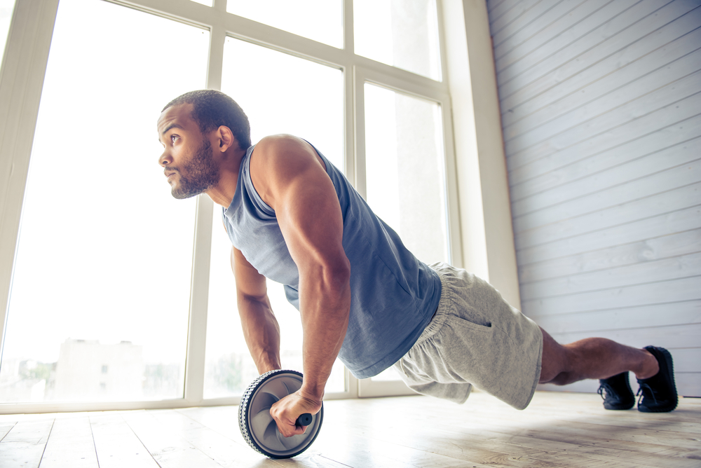 man-doing-ab-roller-at-home