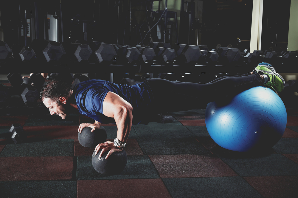 man-doing-push-up-on-exercise-swiss-ball