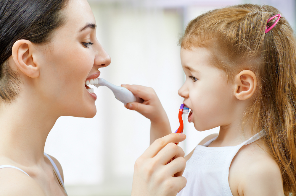 mum-and-daughter-brushing-teeth-for-each-other