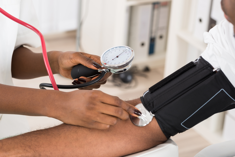Nurse taking high blood pressure of a man