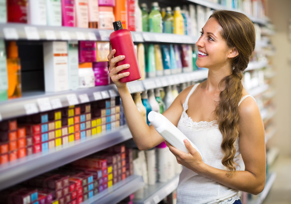 pretty-young-girl-choosing-shampoo-in-the-supermarket