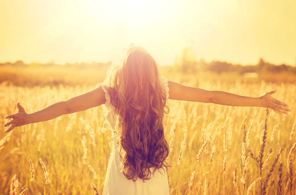 girl-standing-with-open-arms-under-sunlight