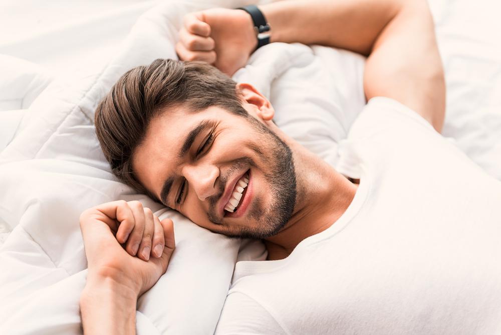 happy-man-lying-in-bed