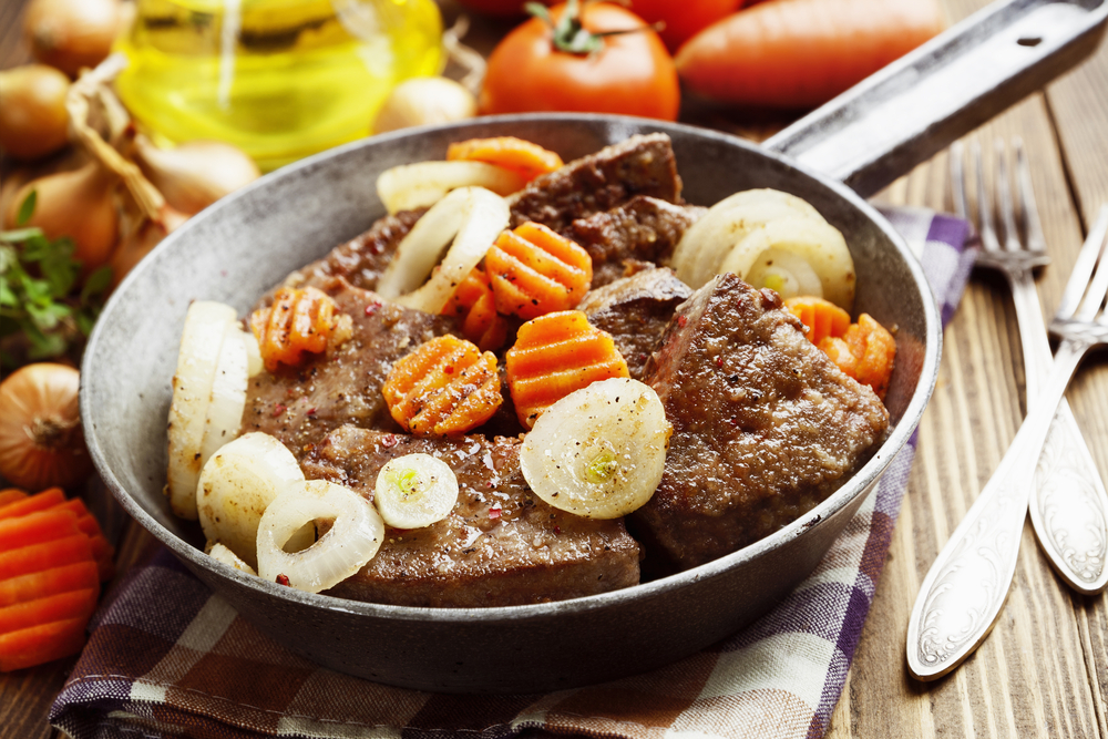 Liver fried with carrot and onion in a frying pan