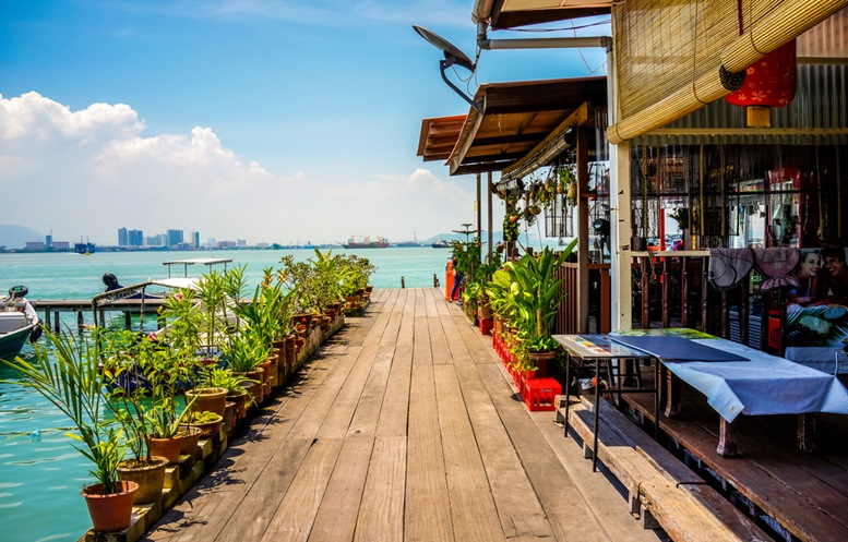 A wooden plank walkway along with a restaurant on the Chew Jetty fishing village