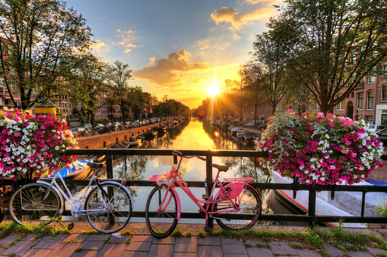 Beautiful sunrise over Amsterdam with flowers and bicycles on the bridge in spring