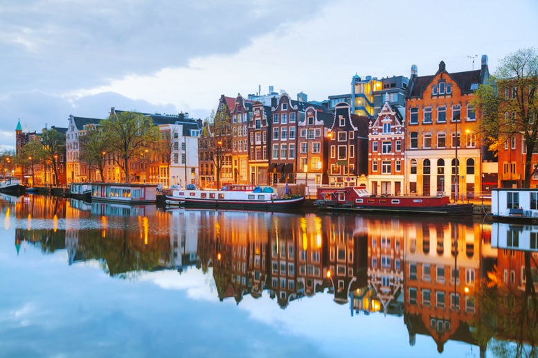 Night city view of Amsterdam, the Netherlands with Amstel river - Featured Image