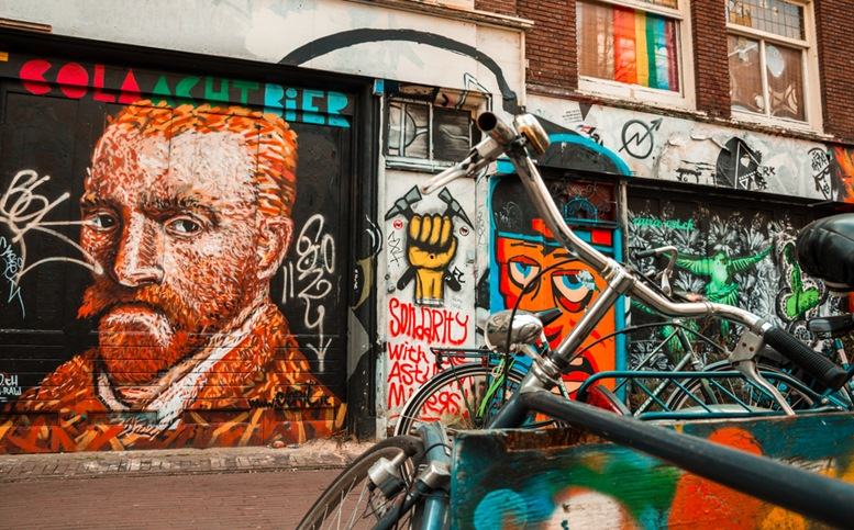 Parked bicycles in front of a graffiti decorated facade with a self-portrait of Vincent Van Gogh, icon of the city.
