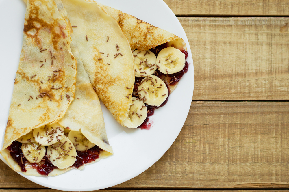 Thin pancakes with banana, sweet jam and chocolate strands