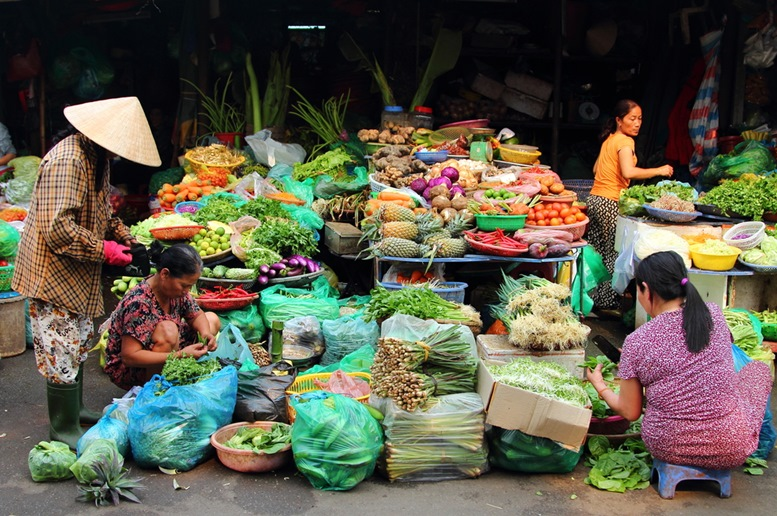 Vietnamese people buying and selling vegetables at Dong Ba market in Hue, Vietnam.