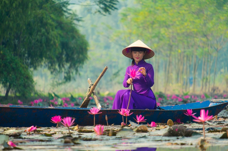 Girl on traditional boat in water lily river visit Huong pagoda