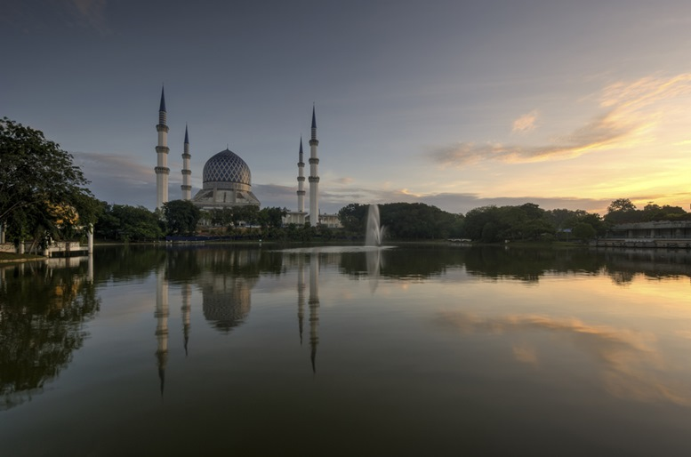 Sultan Salahuddin Abdul Aziz Shah Mosque view during sunrise with reflection in the lake garden