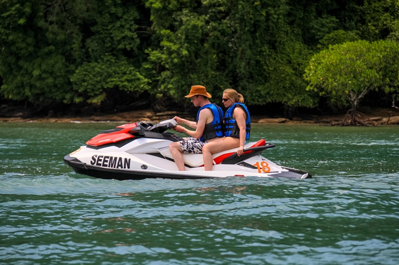 Tourists on jet ski cruising mangrove river