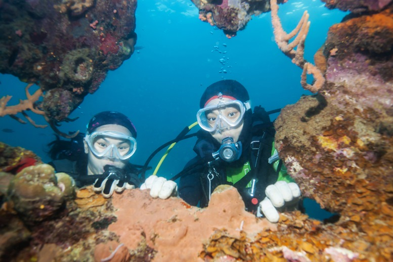 Young scuba divers exploring world war II shipwreck in Coron area, Philippines