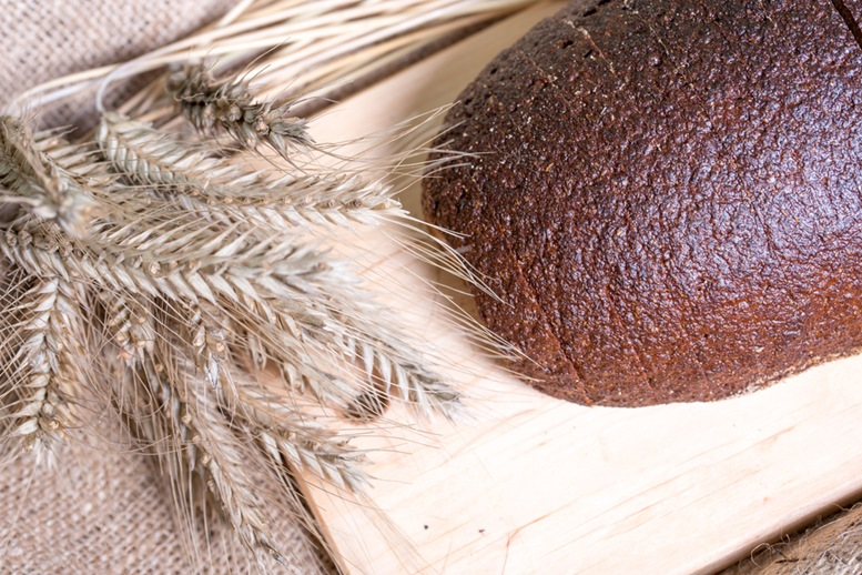brown rye bread loaf and ears of grain. Healthy Whole Grain bread